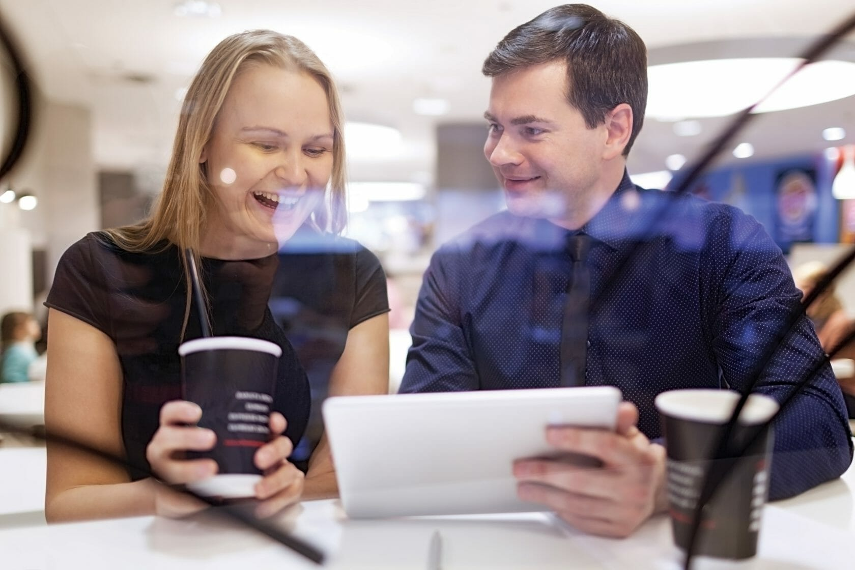 Woman laughs as man shows her something on his tablet as they sit on a table